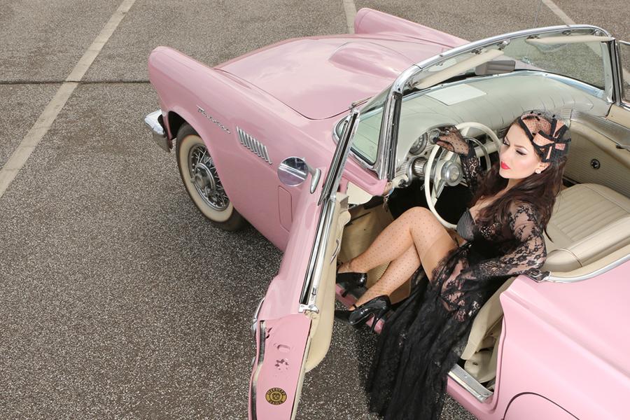 """Acid Doll in einem Ford Thunderbird von 1957 in der Farbe """"Dusk Rose"""". Das Hütchen ist von Dorit Louise Jess, die Heels von Elite Heels, Ohrringe sind von Froilen Adrett. Styling: Alexandra Steinert, Assistenz: Nathaniel Gerong, Foto: Carlos Kella."""